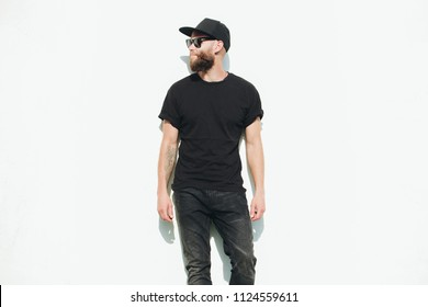 Hipster handsome male model with beard wearing black blank t-shirt with space for your logo or design in casual urban style
