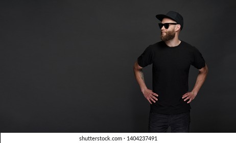 Hipster handsome male model with beard wearing black blank t-shirt with space for your logo or design in casual urban style wth copy space