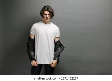 Hipster handsome male model with glasses wearing white blank t-shirt and black jeans with space for your logo or design in casual urban style