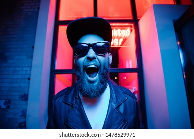 Hipster handsome man on the city streets being illuminated by neon signs. He is wearing leather biker jacket or asymmetric zip jacket with black cap, jeans and sunglasses.