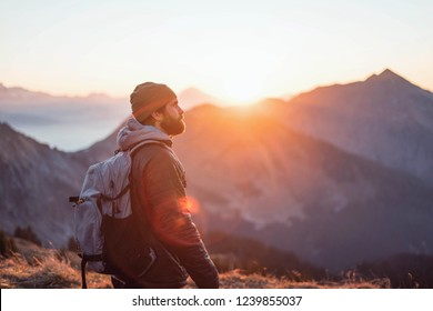hipster with hat and beard wearing casual clothes during a colorful sunset hike
