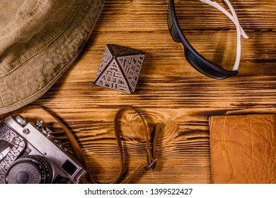 Hipster hat, vintage camera, sunglasses, souvenir pyramid and passport on wooden background. Travel to Egypt. Top view