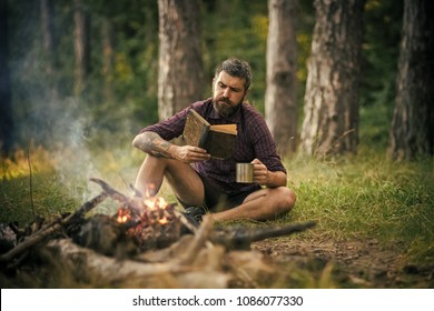 Hipster hiker with book and mug at bonfire in forest. Man traveler read and drink at campfire flame. Summer vacation, activity. Camping, hiking, lifestyle. Sustainable education, environment concept.
