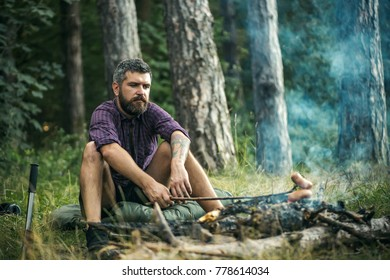 Hipster hiker roast sausages on stick on fire in forest. Picnic, barbecue, cooking food concept. Summer camping, hiking, vacation.