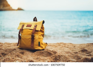 Hipster hiker tourist yellow backpack closeup on background blue sea enjoying sunset ocean horizon, blurred panoramic seascape sunrise blank , traveler relax holiday concept, sunlight view in trip