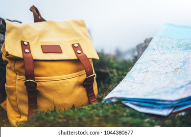 Hipster hiker tourist yellow backpack closeup and navigation map europe on background green grass nature, blurred panoramic landscape, traveler relax holiday concept, view planning way road in trip