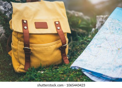 Hipster hiker tourist yellow backpack closeup and navigation map europe on background green grass nature, blurred landscape, traveler relax holiday concept, view planning way road in trip vacation