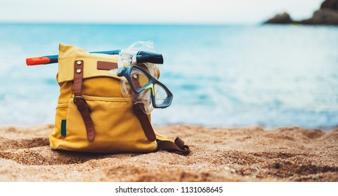 Hipster hiker tourist yellow backpack, swimming mask on background blue sea ocean horizon on sand beach, blur panoramic seascape blank, traveler relax holiday concept, sunlight view in trip vacation