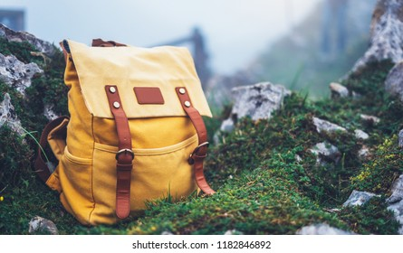 Hipster hiker tourist yellow backpack on background green grass nature in mountain, blurred panoramic landscape, traveler relax holiday concept, planning wayroad in trip vacation, travel adventure