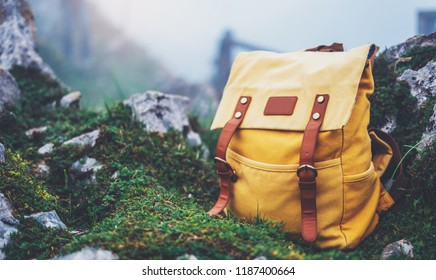 Hipster hiker tourist yellow backpack on background grass nature in mountain, blurred panoramic landscape, traveler relax holiday concept, view planning wayroad in trip vacation, travel adventure