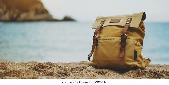 Hipster hiker tourist yellow backpack closeup on background blue sea enjoying sunset ocean horizon, blurred panoramic seascape blank mockup, traveler relax holiday concept, sunlight view in vacation