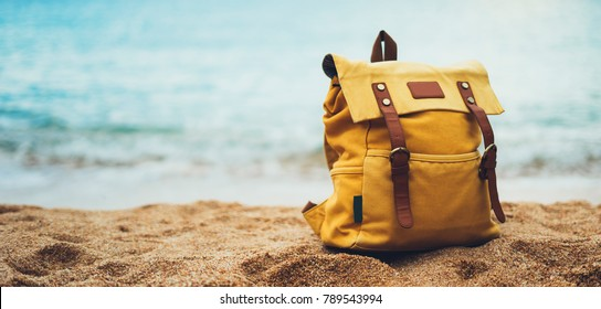 Hipster hiker tourist yellow backpack closeup on background blue sea enjoying sunset ocean horizon, blurred panoramic seascape sunrise blank mockup, traveler relax holiday concept, sunlight view