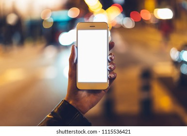 hipster hold in hands clean gadget mobile phone closeup, blank screen smartphone on background bokeh light in night atmospheric city, mockup street, lifestyle online wifi internet concept, lights