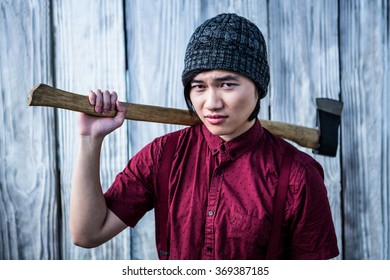 Hipster holding a axe on wooden background