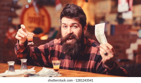 Hipster holds money, cash to buy more alcohol. Man with drunk face sit alone at bar counter. Buy drinks concept. Guy spend leisure in bar drinking cocktail, defocused background.