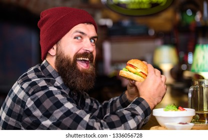 Hipster hungry man eat burger. Man with beard eat burger menu. Brutal hipster bearded man sit at bar counter. High calorie food. Cheat meal. Delicious burger concept. Enjoy taste of fresh burger.
