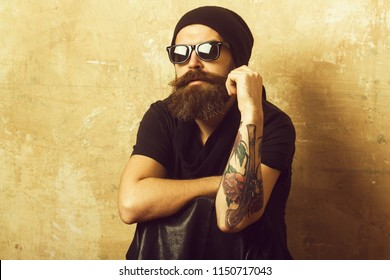 Hipster in leather jacket and hat with glasses. Man with long beard and mustache. Guy with serious face. Fashion model on textured wall background. Biker fashion and beauty.