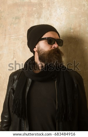 Hipster in leather jacket and hat with glasses. Man with long beard and  mustache. a65c210fd1db