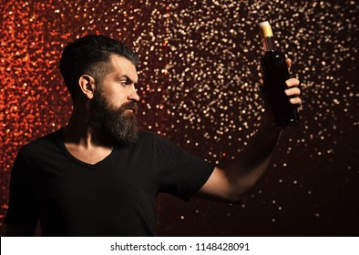 Hipster with long beard in black tshirt hold wine. Bearded man with bottle on bokeh background. Party, holidays celebration. Fashion, style concept. Bad habit, alcohol addiction.