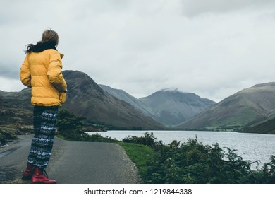 Hipster looking tourist  dressed in outdoor wear standing on countryside road and enjoying beautiful view on scenic mountain valley with lake in rural Uk.Human and nature.Solitude and tranquility.