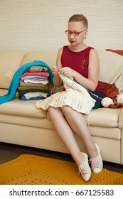 Hipster looking woman  in glasses knitting at home, near her lies heap of knitted clothes