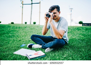Hipster male bloger focusing and making photos sitting o green grass in parkk with design sketches.Professional skilled photographer taking pictures on stylish vintage camera on university territory