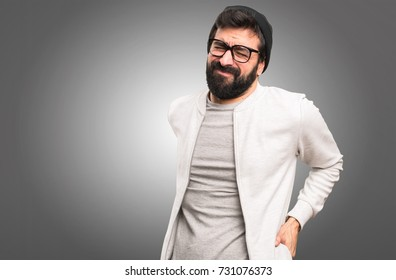 Hipster man with back pain on grey background