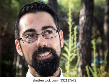 Hipster man with beard and hat on the beach and the forest