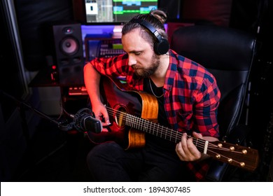 Hipster man with beard in headphone is playing guitar and sining his new song in stereo studio to record brand-new track