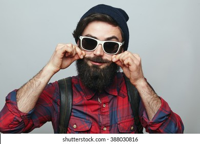 Hipster man with beard wearing sunglasses adjusting his mustaches while standing against grey background