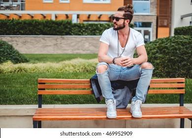 Hipster com pão homem sentado no banco do parque em um dia ensolarado