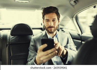 Hipster man in car. Typing text message on mobile phone. Filter vintage