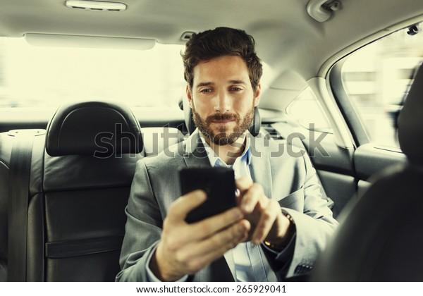Hipster Mann im Auto. Eingabe von Textnachrichten auf dem Handy. Filtervintage
