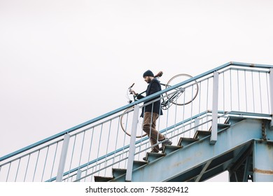 Hipster man carry bicycle down the stairs