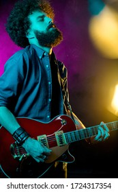 Hipster man with curly hair play with passion red guitar in neon lights. Rock musician is playing electrical guitar.
