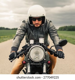 Hipster Man Driving Vintage Style Cafe Racer Motorcycle On The Road