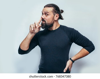 the hipster man is emotionally picking his nose. Crazy emotions. Hipster wearing black blank t-shirt with space for your logo. The emotional portrait.