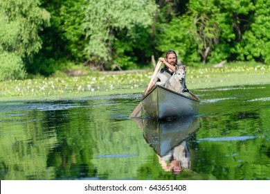 Hipster man enjoying with his dog in the canoe on the swamp landscape.Copy space