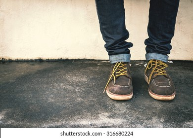 Hipster man with fashion brown leather boots on the ground