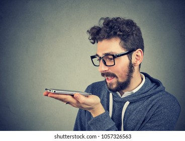 Hipster man in glasses using a smart phone voice recognition function isolated on wall background