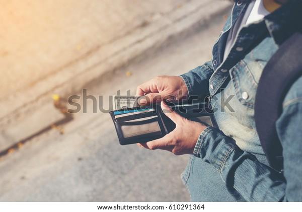 ヒップスターの男性は、クレジットカードとお金の山で財布を手にします。