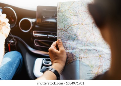 Hipster man holding in male hands and looking on navigation map in auto, tourist traveler hiker driving on background panoramic view way road, trip in transportation, person sitting on backdrop window