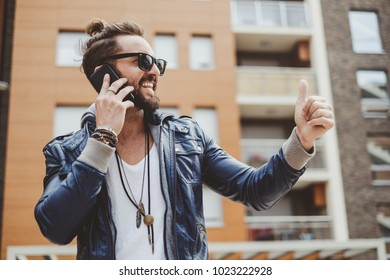 Hipster man holding thumb up and smiling while talking on the phone
