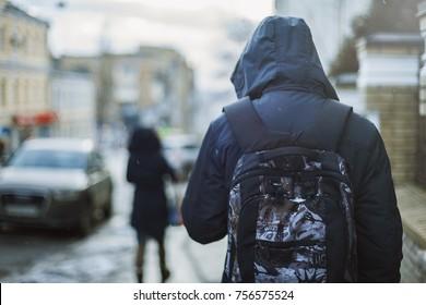 Hipster man in hood walking through city street