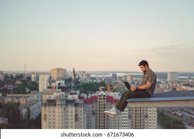 Hipster man with a laptop on the edge of the roof. Freelancer at work. Wireless mobile Internet. He works on the Internet.