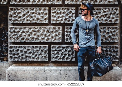 Hipster man leaning on the wall and waiting while holding his leather bag