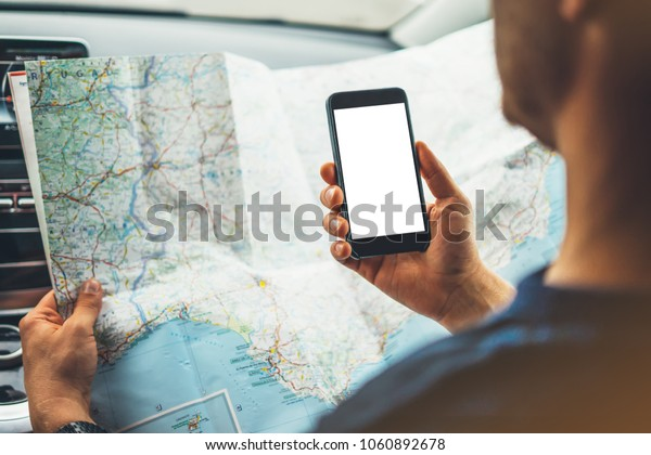 Hipster man looking on navigation map, tourist traveler driving and holding in male hands smartphone gps with clean screen display, panoramic view way road, trip in transportation from window auto