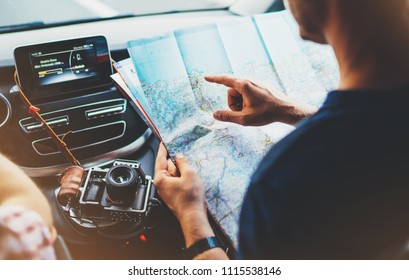 Hipster man looking and point finger on location navigation map in car, tourist traveler driving and hold in male hands europe cartography, view and plan tourist way road, trip in transportation