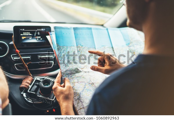 Hipster man looking point finger on location navigation map in car, tourist traveler driving and hold in male hands europe cartography, plan tourist way road, trip in transportation from window auto