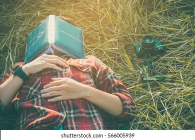 hipster man lying down on grassland napping tired after reading book with nature around outside